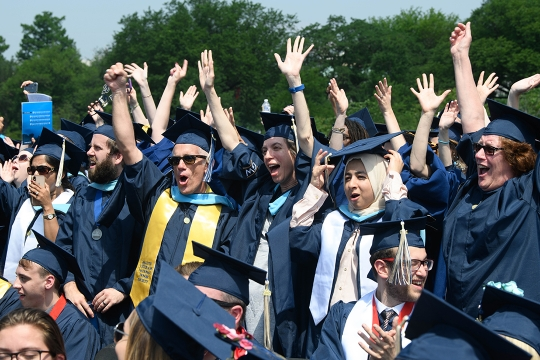 photo - Students cheer at the 2019 GW University Commencement on the National Mall