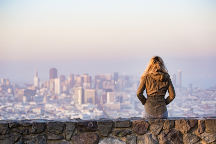 Woman with back turned looks at city skyline in distance.