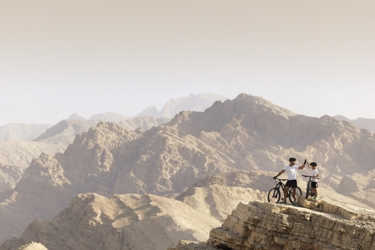 A father and son on mountain bikes look over a mountain peak